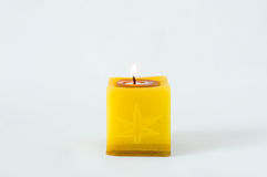 Den en gula stearinljuset skiner i vit bakgrund Royaltyfria Foton