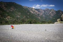 Den enda kulöra slags solskydd på en tom strand mellan bergen på kusten Royaltyfria Bilder