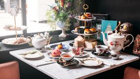 Den engelska eftermiddagteservisen inklusive varmt te, bakelse, sconeser, smörgåsar och mini- pajer marmorerar på den bästa tabel arkivbilder