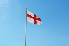 Den engelska flaggan flyger mot en blå himmel Arkivbilder
