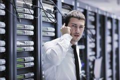 Den engineer samtal vid telefonen på nätverkslokal Arkivfoto