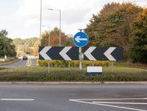 Den England vägkarusellen undertecknar riktningar inga bilar Arkivfoto