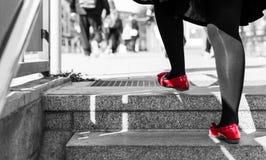 Den enkla äldre kvinnan med svart strumpbyxor och den svarta klänningen går uppför trappan med röda skor Royaltyfri Foto