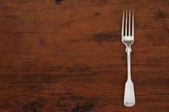 Den enkla antikviteten försilvrar gaffeln på en tom trätabell med ett kopieringsutrymme arkivbild