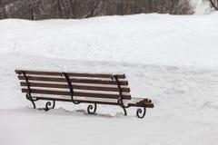 Den enkla bänken som täckas med insnöad vinter, parkerar Royaltyfria Foton