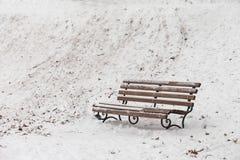 Den enkla bänken som täckas med insnöad vinter, parkerar Royaltyfri Fotografi