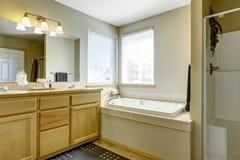 Den enkla badruminre med badet badar i hörnet Arkivbild