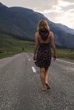 Den enkla barfota kvinnan promenerar bergvägen Lopp, turism och folkbegrepp Arkivbild