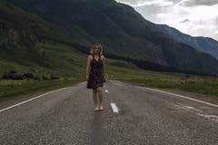 Den enkla barfota kvinnan promenerar bergvägen Lopp, turism och folkbegrepp Royaltyfria Foton