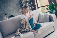 Den enkla frustrerade utmattade kvinnan sitter på en soffa i en livi fotografering för bildbyråer