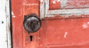 Den enkla gamla knoppen för 20-taleradörren med den skelett- nyckelhålet på en gammal målarfärg gå i flisor, den röda dörren Fotografering för Bildbyråer