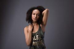 Den enkla härliga le afrikansk amerikankvinnan med handen in mot huvudet över grå färger kopierar upp utrymme royaltyfri fotografi