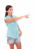 Den enkla kvinnan i kort jeans som pekar till henne, lämnade royaltyfria foton