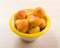 Den enkla matsammansättningen med aprikons i bunken på den unika täckningcloseupen Arkivfoton