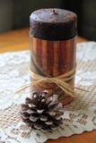 Den enkla platsen av den Americana stearinljuset och pineconen snör åt på tabelllöparen Royaltyfri Bild