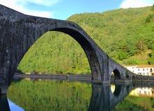 Den enorma bågen av en medeltida bro för puckelrygg royaltyfri fotografi