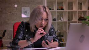 Den enorma blonda caucasian kvinnan ser exakt på hennes telefon och tryckande på skärm, medan sitta på arbetsplatsen inomhus stock video