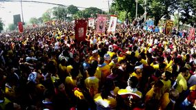 Den enorma folkmassan av katolska fantaster konvergerar för att sammanfoga i processionen av den svarta nazarenen lager videofilmer