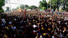 Den enorma folkmassan av katolska fantaster konvergerar för att sammanfoga i processionen av den svarta nazarenen stock video