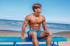 Den enorma muskulösa unga grabben i blått simmar kortslutningar Arkivbild