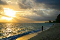 Den enorma solnedgångstranden går efter den tropiska stormen, guld- solstrålsolstrålar som öppnar mörk molnig himmel royaltyfri fotografi