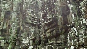 Den enorma stenen vänder mot på väggarna av en forntida tempel Cambodja Bayon stock video