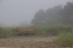 Den ensamma bänken på en dimmig dag - lagerföra fotoet arkivfoton