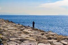 Den ensamma fiskaren med stången på vaggar, golfen av Naples, Italien Royaltyfria Bilder