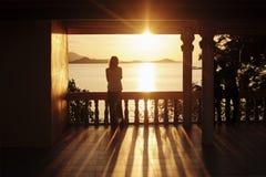 Den ensamma flickan står på terrassen och beundrar inställningssolen Arkivfoton