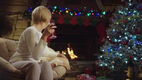 Den ensamma gamla damen dricker vin på julnatt arkivfilmer