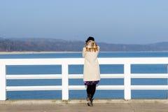 Den ensamma härliga ledsna flickan står på pir på en solig varm höstafton på havet Royaltyfri Bild