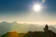 Den ensamma ledsna personen sitter på toppmöte av berget Arkivbild