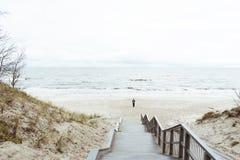 Den ensamma mannen går på stranden längs kustlinjen, mora, arkivbild