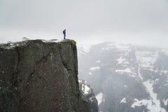 Den ensamma mannen på vaggar, handelsresandeanseendet på den höga kanten av klippan och att se berg i mist royaltyfri fotografi