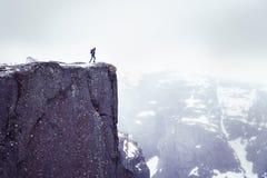 Den ensamma mannen på vaggar, handelsresandeanseendet på den höga kanten av klippan och att se berg i mist royaltyfria bilder