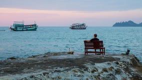 Den ensamma mannen sitter på en bänk på kusten som håller ögonen på fiskebåtarna Arkivbild