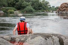 Den ensamma mannen sitter vid floden i en röd väst royaltyfria bilder