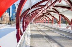 Den ensamma personen som promenerar ett stål, täckte bron på en vinterdag royaltyfria foton