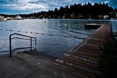 Den ensamma Pier At The Swimming Lanes på den Meydenbauer stranden parkerar i Bellevue efter timme efter mörker royaltyfria bilder