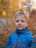 Den ensamma pojken med ett leende i höst parkerar royaltyfria foton