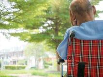 Den ensamma sickmanen i hans 77 år gammalt sammanträde i rullstol på parkerar Royaltyfri Foto