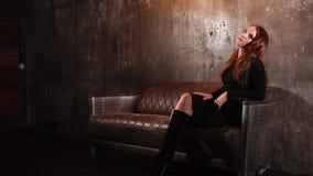 Den ensamma sinnliga rödhårig mankvinnan är avslappnande på en lyxig soffa i en korridor arkivfilmer
