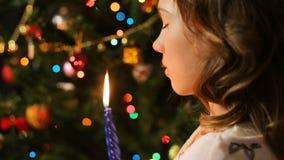 Den ensamma tonåringinnehavstearinljuset och danande en önska nära dekorerade granträdet lager videofilmer