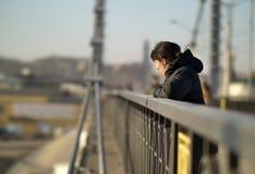 Den ensamma unga brunettflickan står på bron på en solig dag royaltyfri fotografi