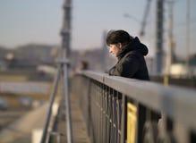 Den ensamma unga flickan st?r p? bron p? en solig dag arkivfoto