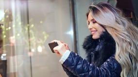 Den entusiastiska nätta kvinnan som tar bilden av julgåvan shoppar in, exponeringsglasfönstret genom att använda smartphonen lager videofilmer