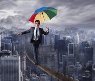 Den Equilibrist affärsmannen går på ett rep med paraplyet över staden Begrepp av betaget problemen och positivityen arkivbilder