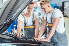 Den erfarna automatiska mekanikern som kontrollerar delarna av en bil i en modern reparation, shoppar fotografering för bildbyråer