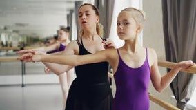 Den erfarna balettläraren undervisar unga kvinnliga studenter balettförehavanden och positioner, medan flitiga flickor är arkivfilmer