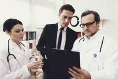 Den erfarna doktorn med sjuksköterskan och den besvärade affärsmannen ser resultat av läkarundersökning royaltyfria bilder